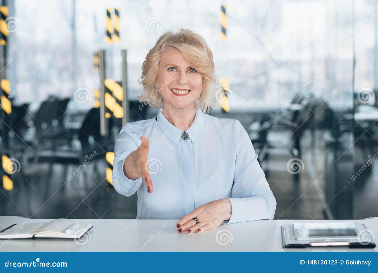 Senhora superior amigável que dá boas-vindas à empresa bem sucedida