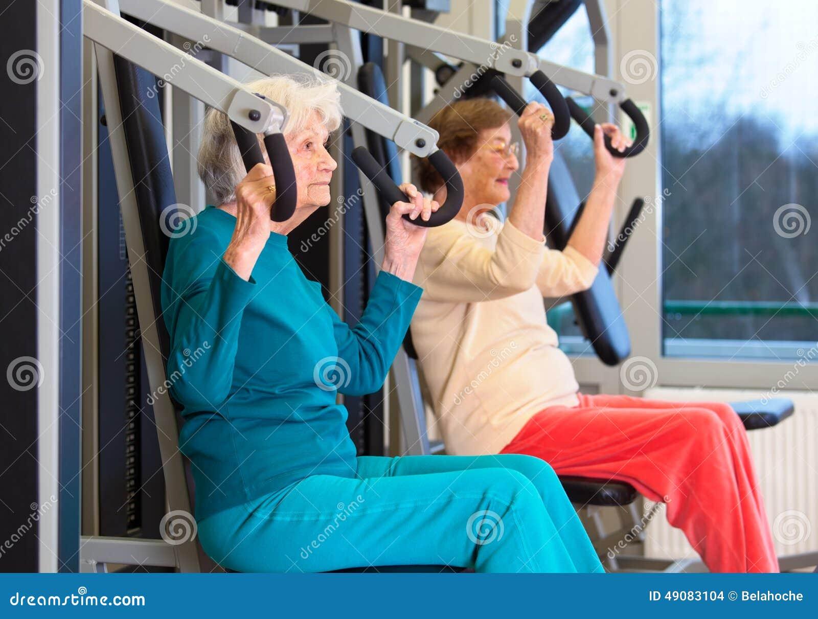 Senhoras idosas saudáveis no exercício da imprensa da caixa