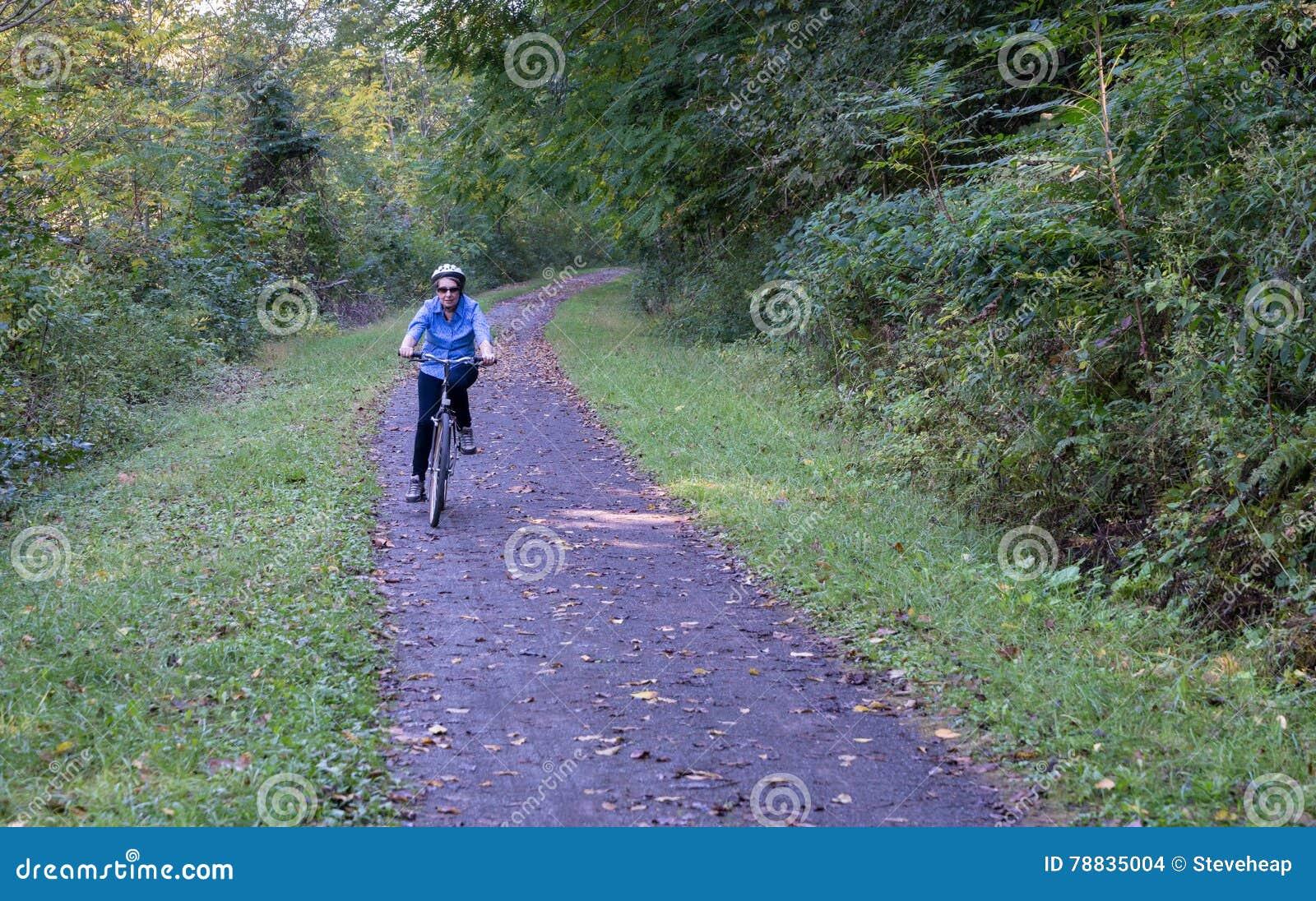 Senior adult woman cycles towards camera