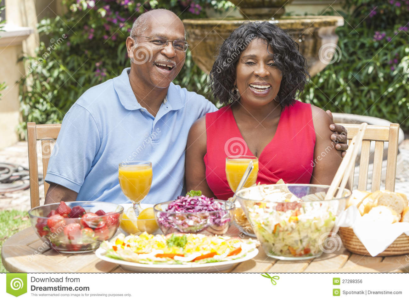 ... African American couple eating healthy food at a picnic table outside