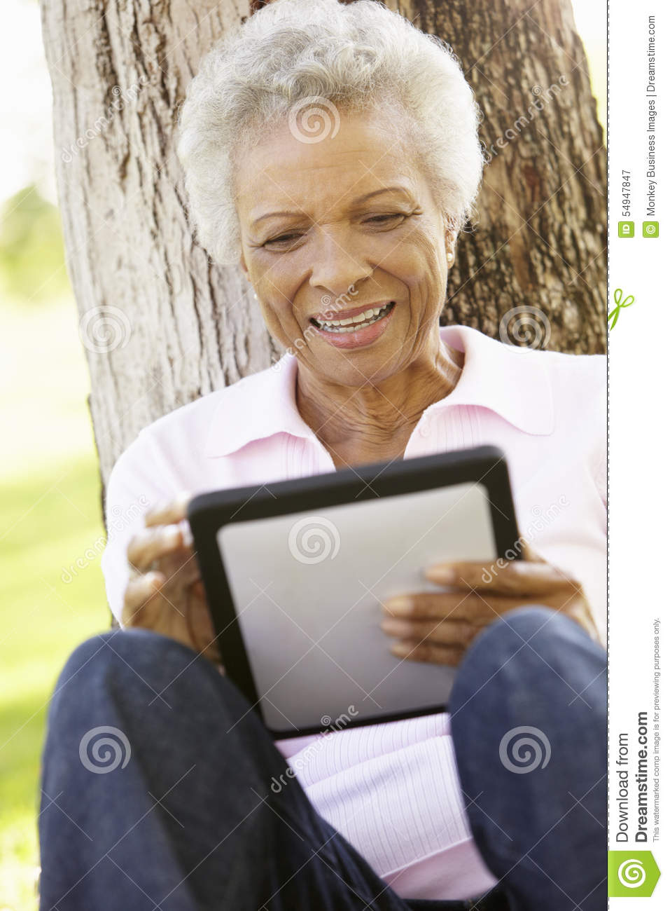 Senior African American Woman In Park Using Tablet Computer