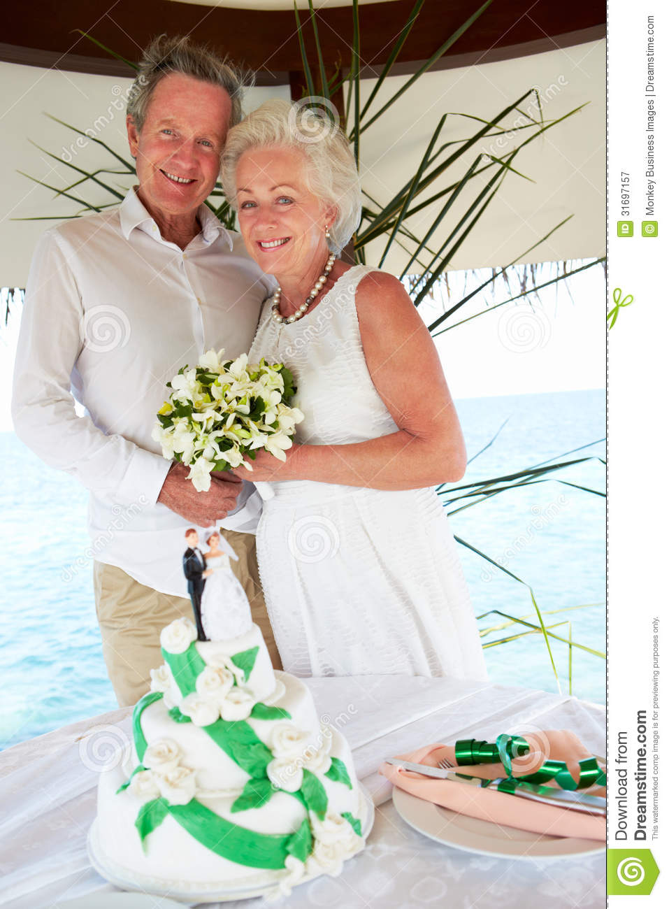 Senior Beach Wedding Ceremony With Cake In Foreground
