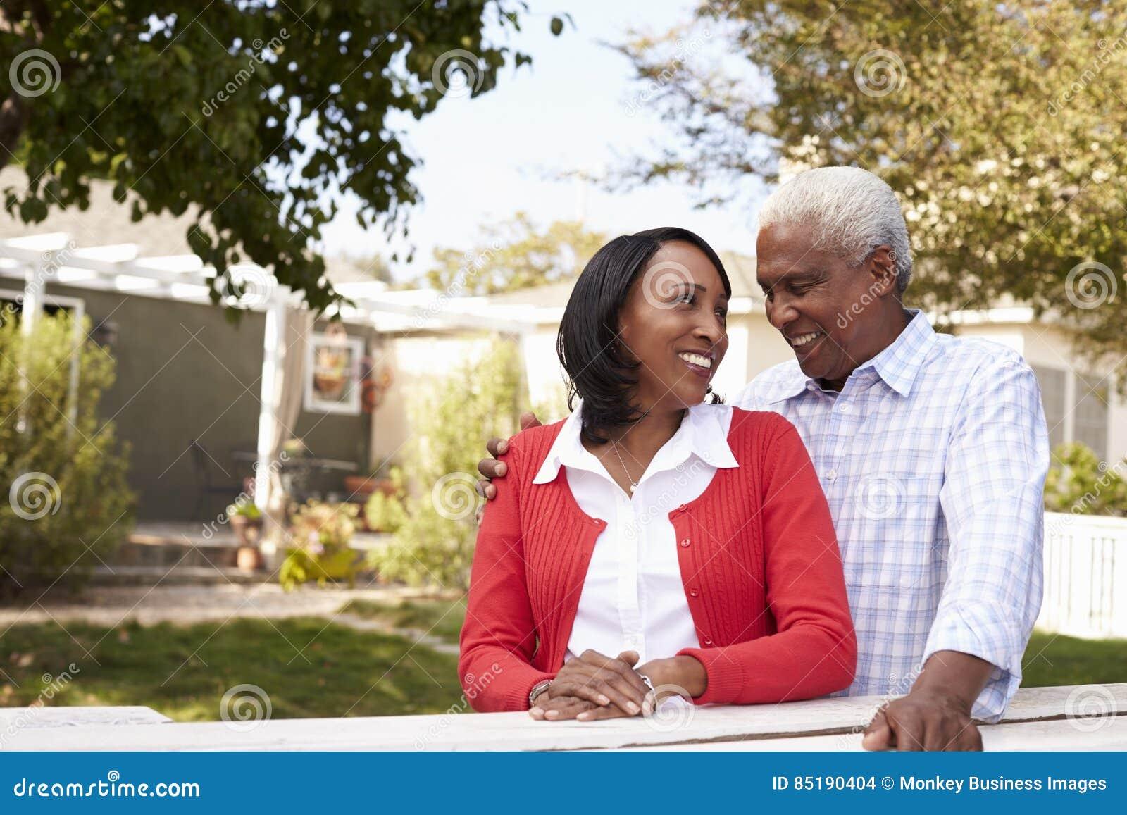 Senior black couple standing outside their new house