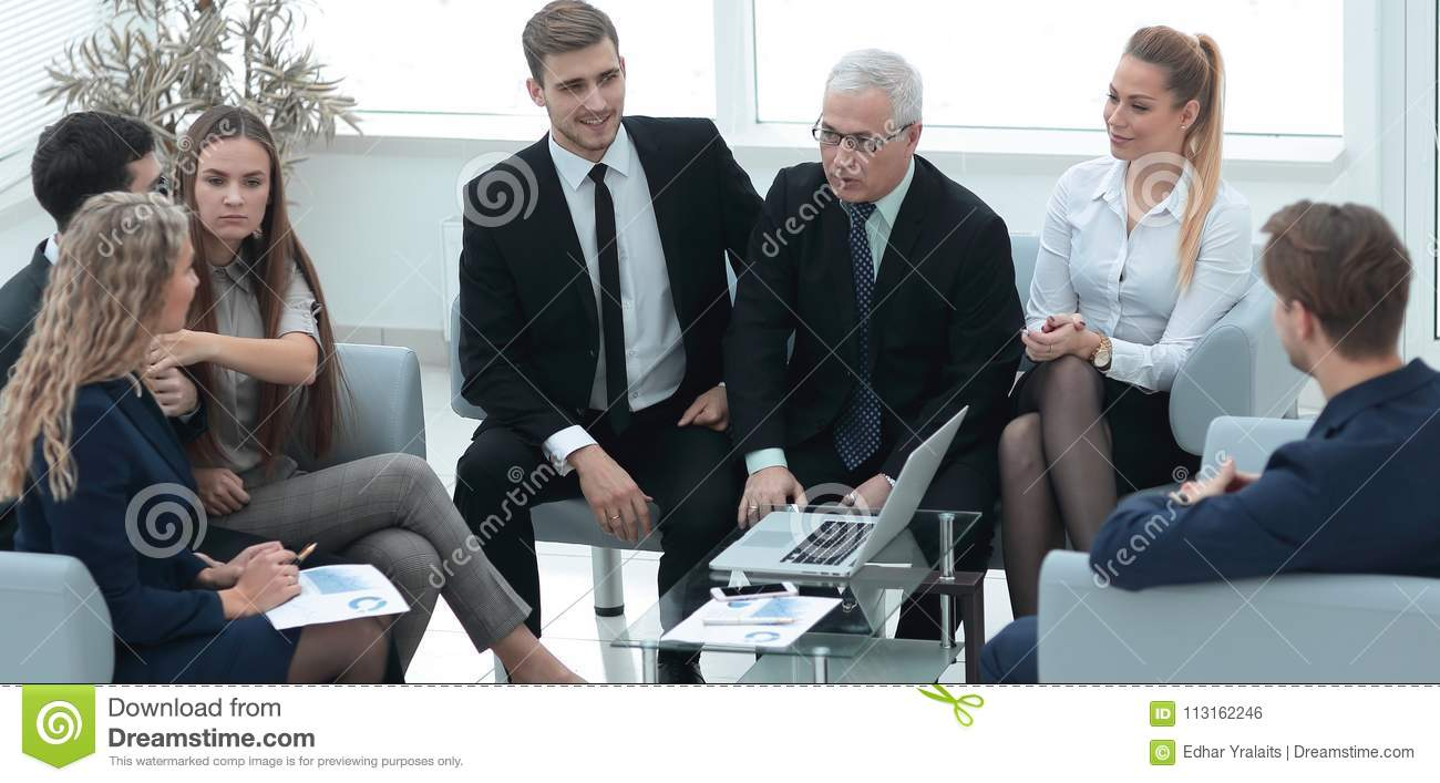 Senior businessman and business team sitting in the lobby of the modern office.