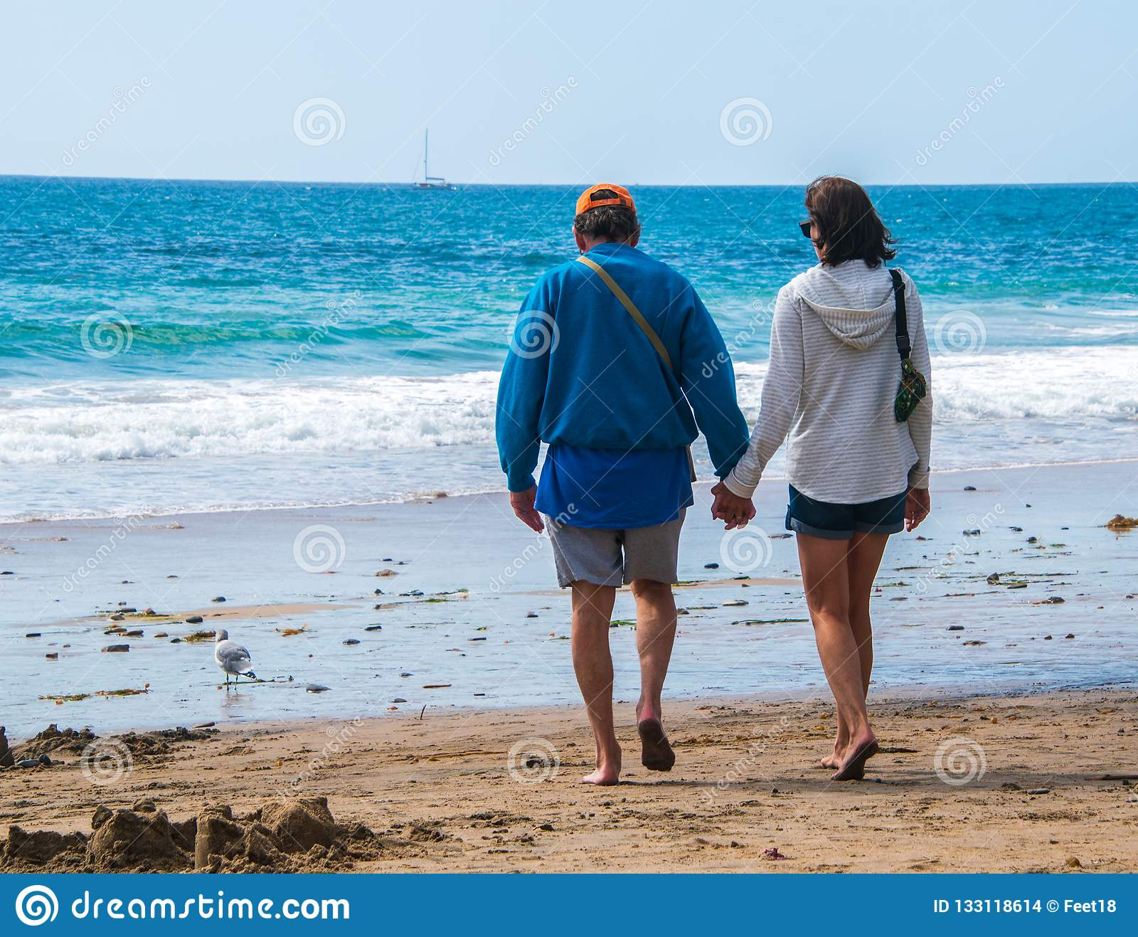 Senior citizen baby boomer male and female caucasian couple walking on the beach towards the ocean holding hands.