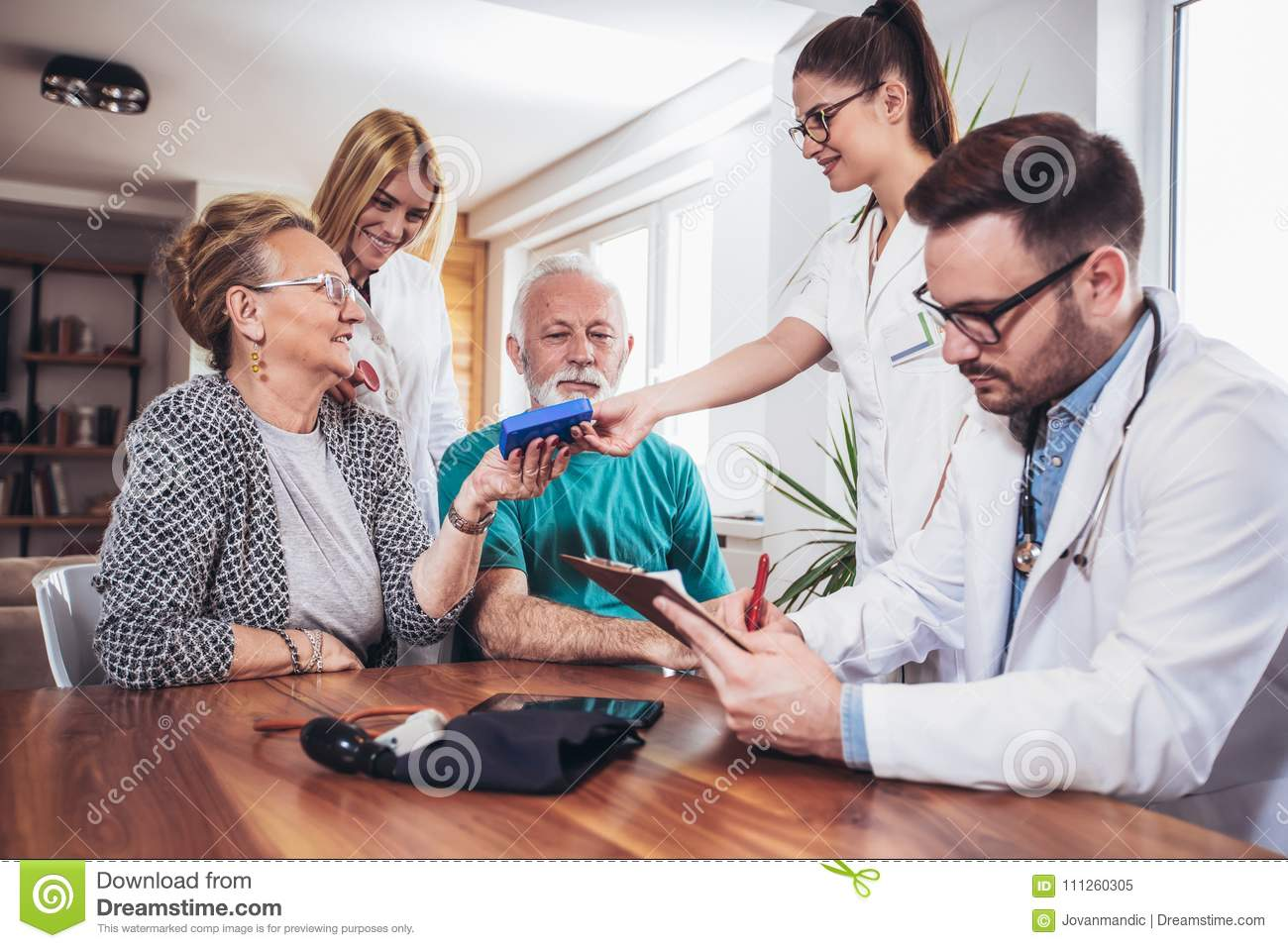 Senior Couple In Discussion With Health Visitor At Home.