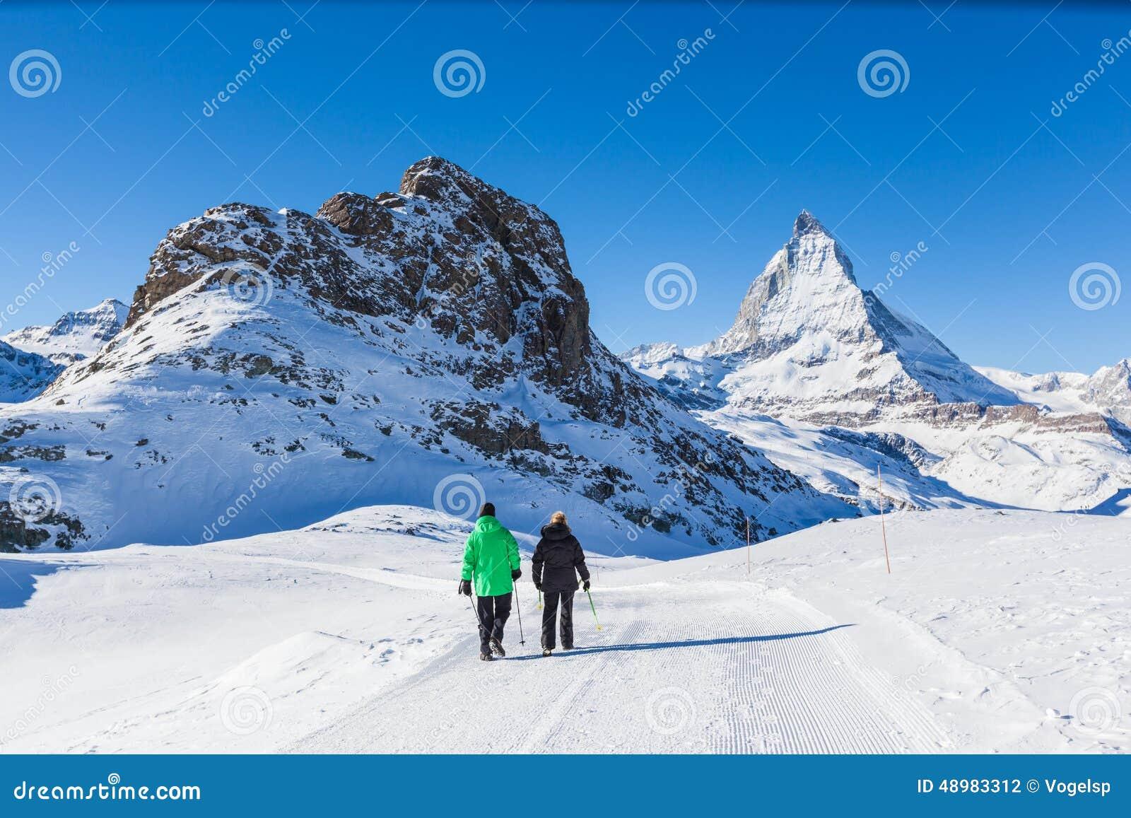 Senior couple doing winter hiking near Matterhorn, Zermatt