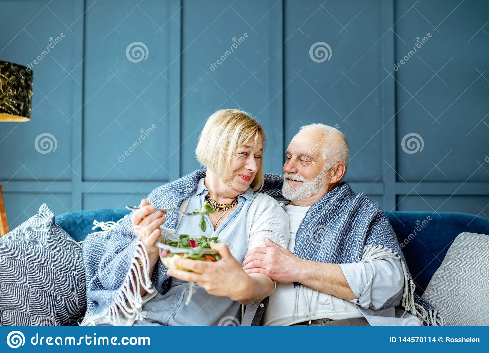 Senior couple eating healthy salad on the couch at home