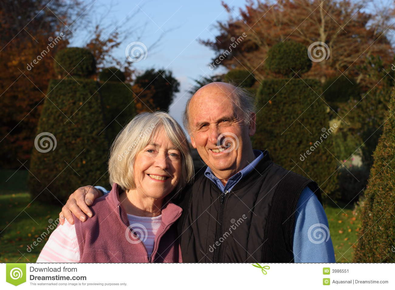 Senior couple embrace in formal gardens.