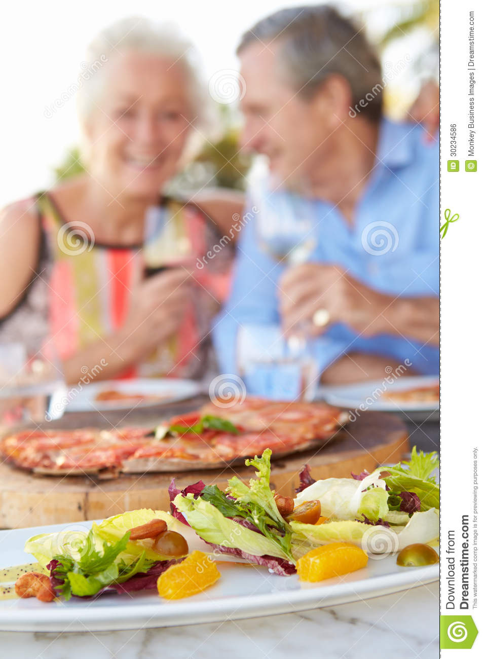 Senior couple enjoying meal in outdoor restaurant royalty for Meal outdoors