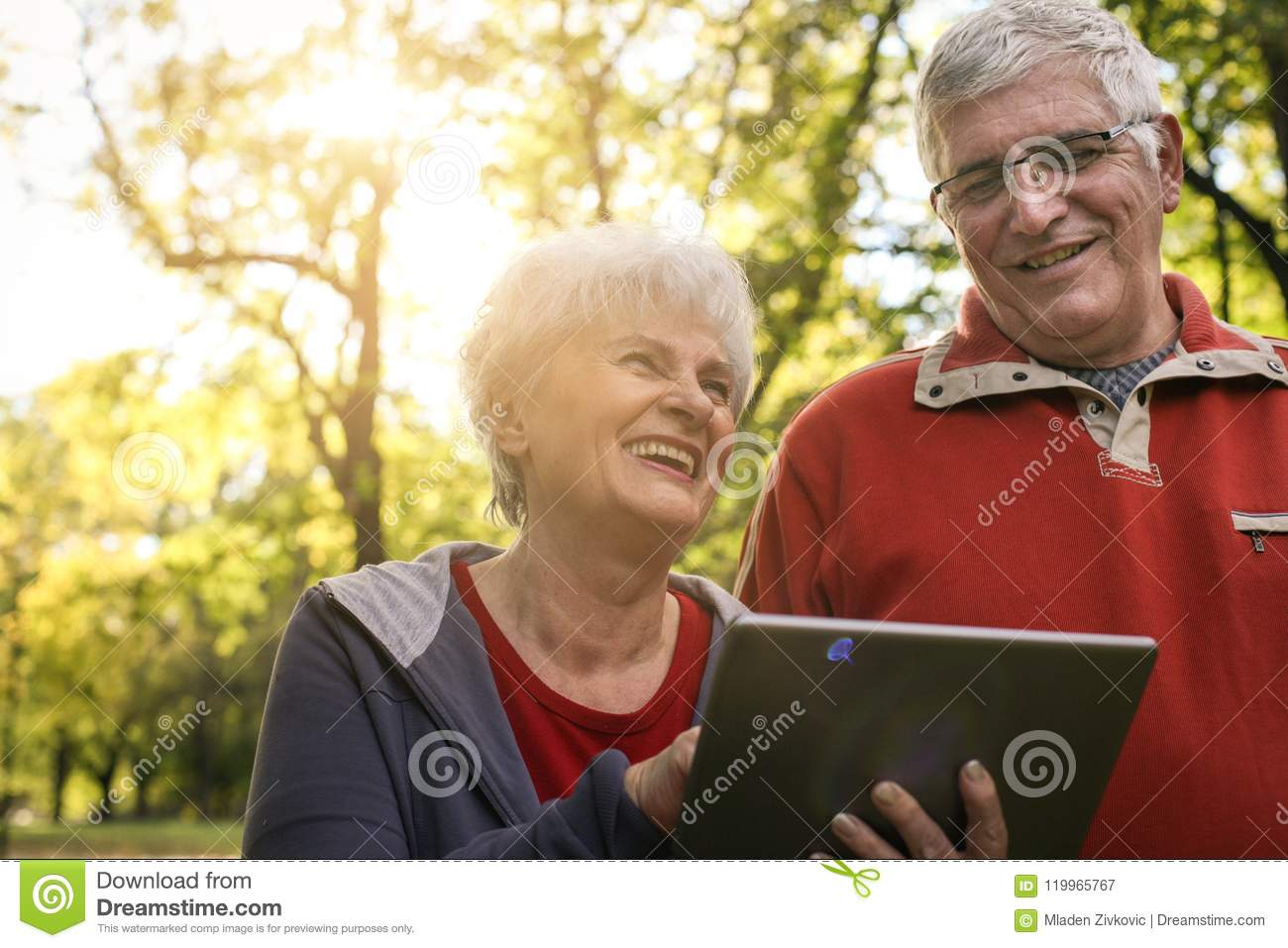 Senior couple enjoying in park together and using digit