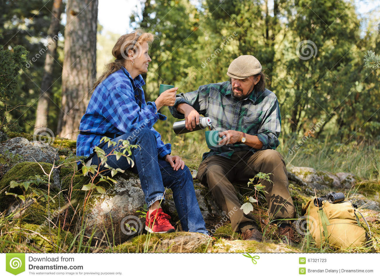 Senior couple having a coffee break in the forest