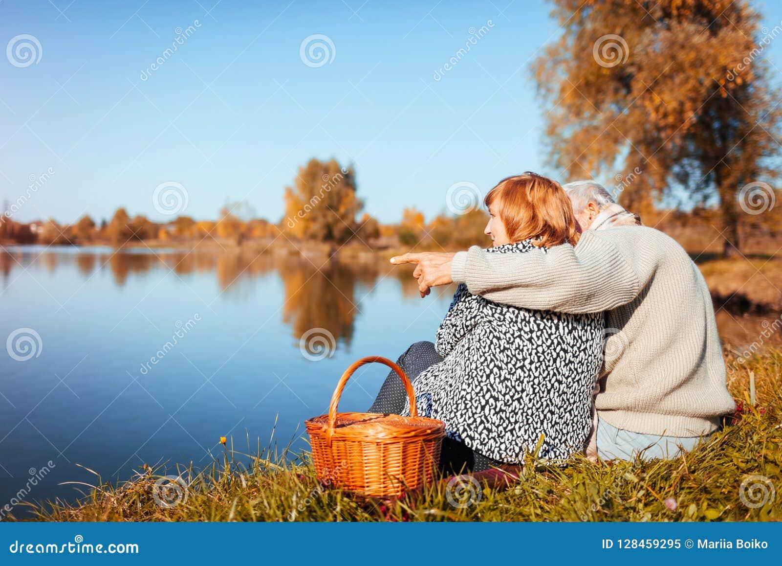 Senior couple having picnic by autumn lake. Happy man and woman enjoying nature and hugging