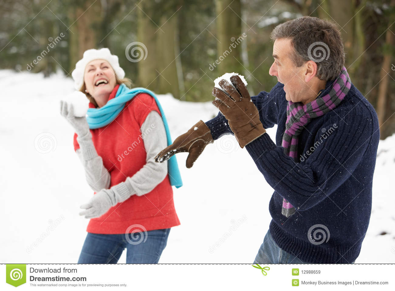 Senior Couple Having Snowball Fight In Snow