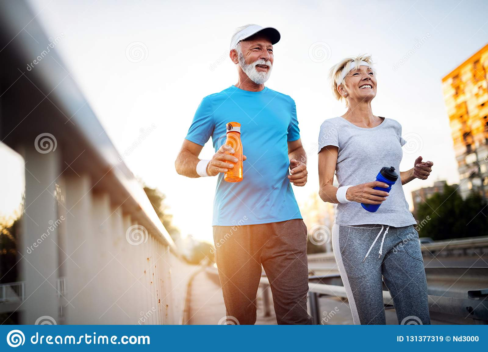 Mature couple jogging and running outdoors in city