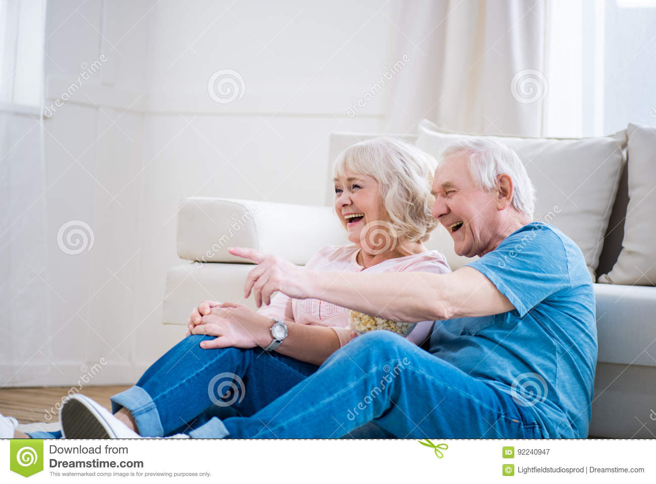 Senior couple laughing and sitting on floor, man pointing