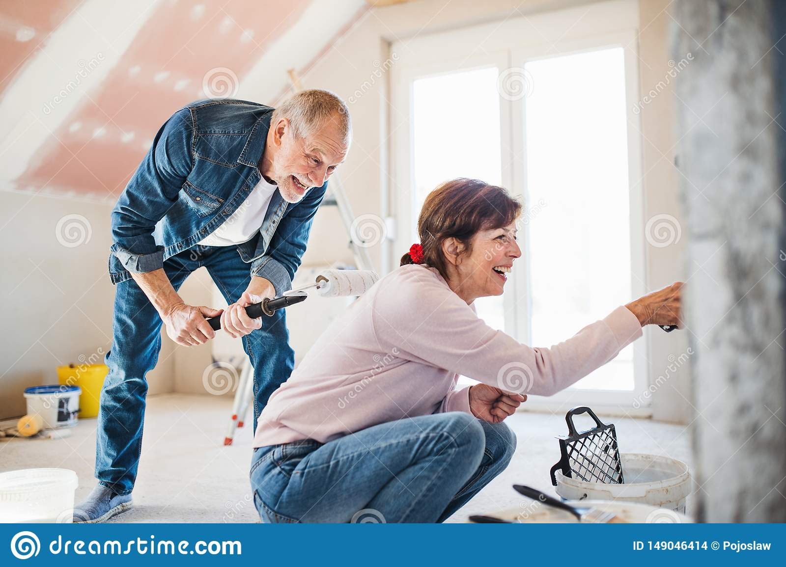 Senior couple painting walls in new home, relocation concept.