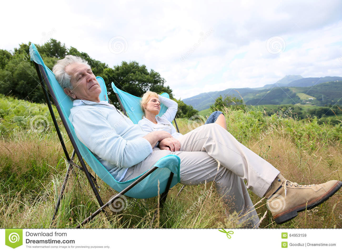 Senior couple relaxing in camping chairs