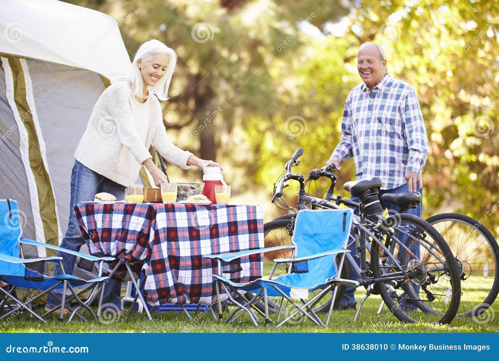 Senior Couple Riding Bikes On Camping Holiday