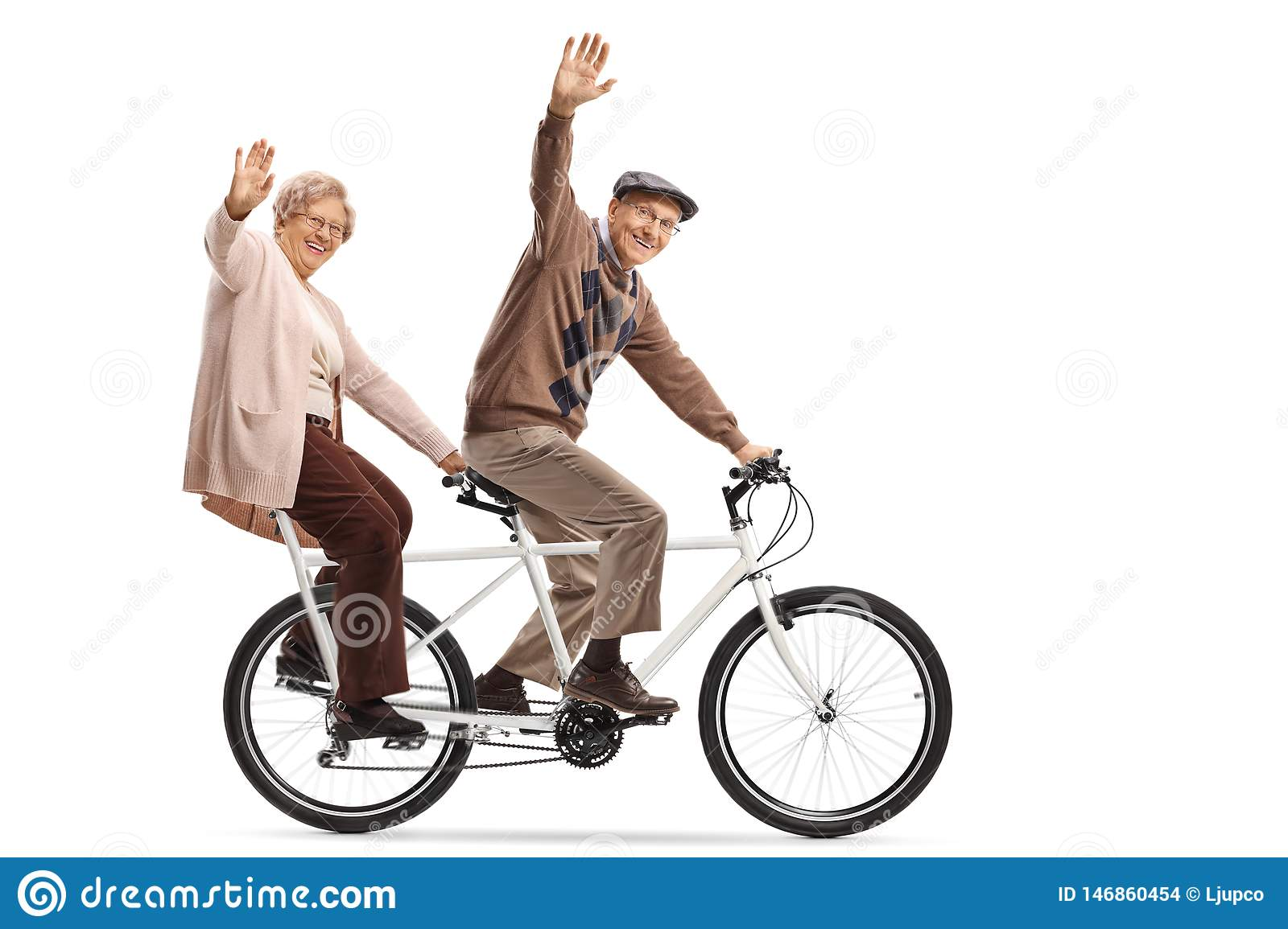 Senior couple riding a tandem bycicle and waving