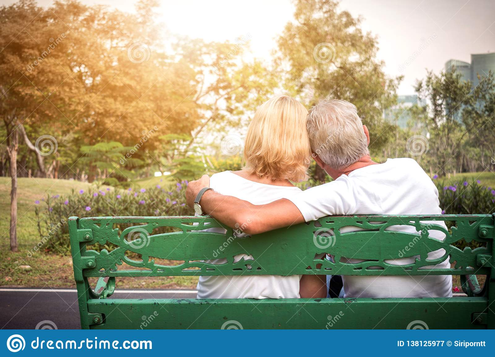 Senior couple siting on a bench and having romantic and relaxing time in a park