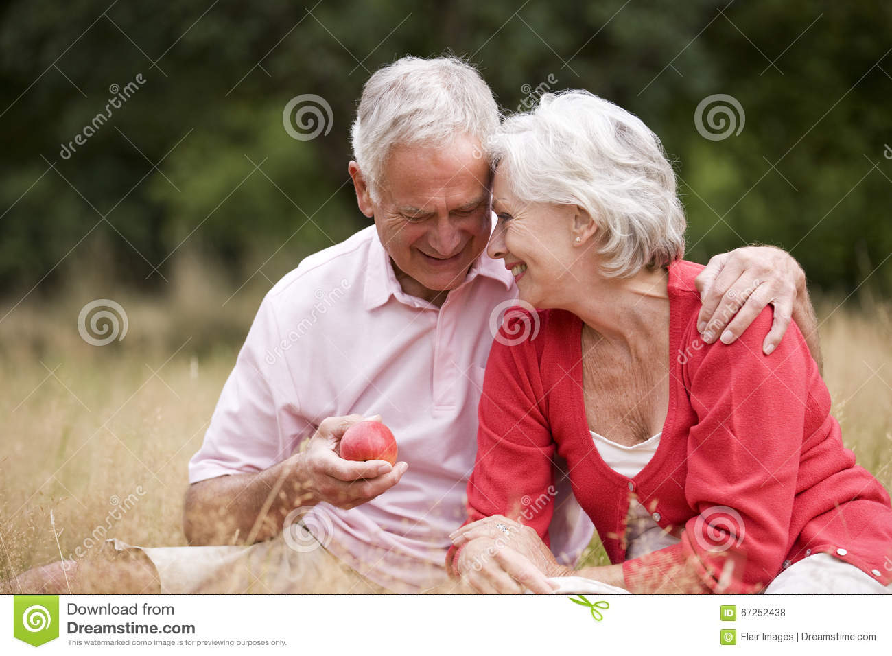 A senior couple sitting on the grass, man holding an apple
