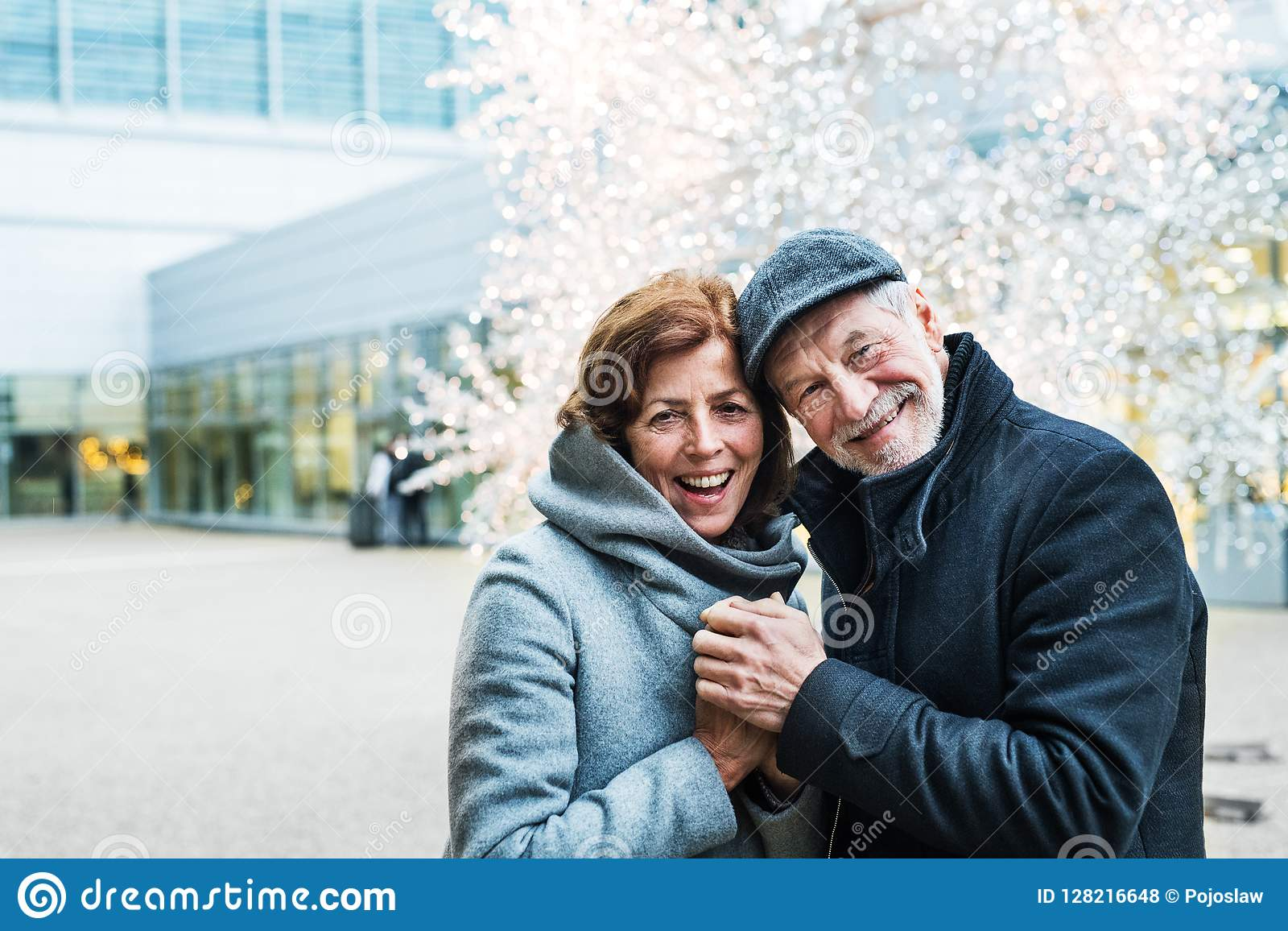 A senior couple standing outdoors in front of shopping center at Christmas time.