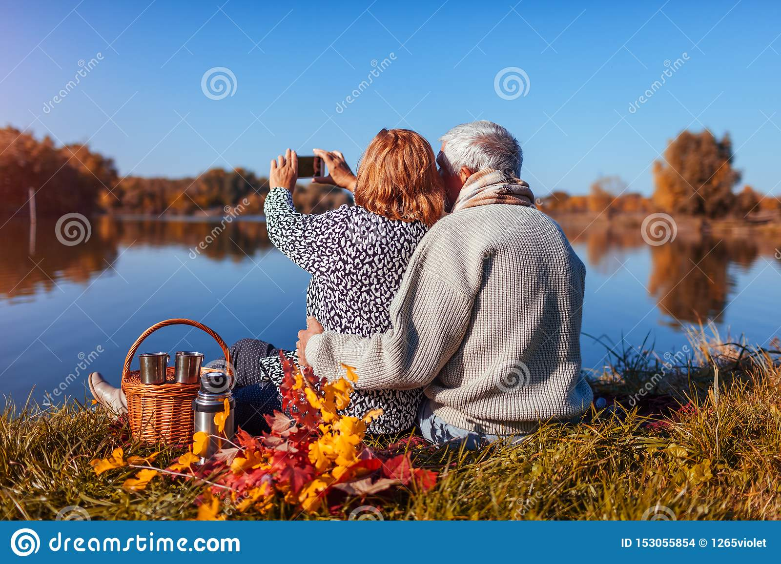 Senior couple taking selfie while having picnic by autumn lake. Happy man and woman enjoying nature and hugging