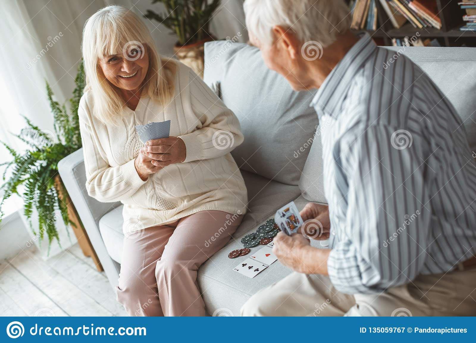 Senior couple together at home retirement concept playing poker sly grin