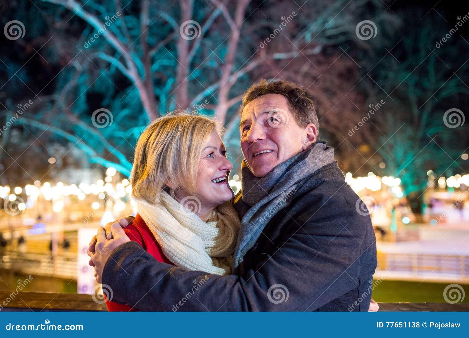 Senior couple walking in night city. Winter, Historical building