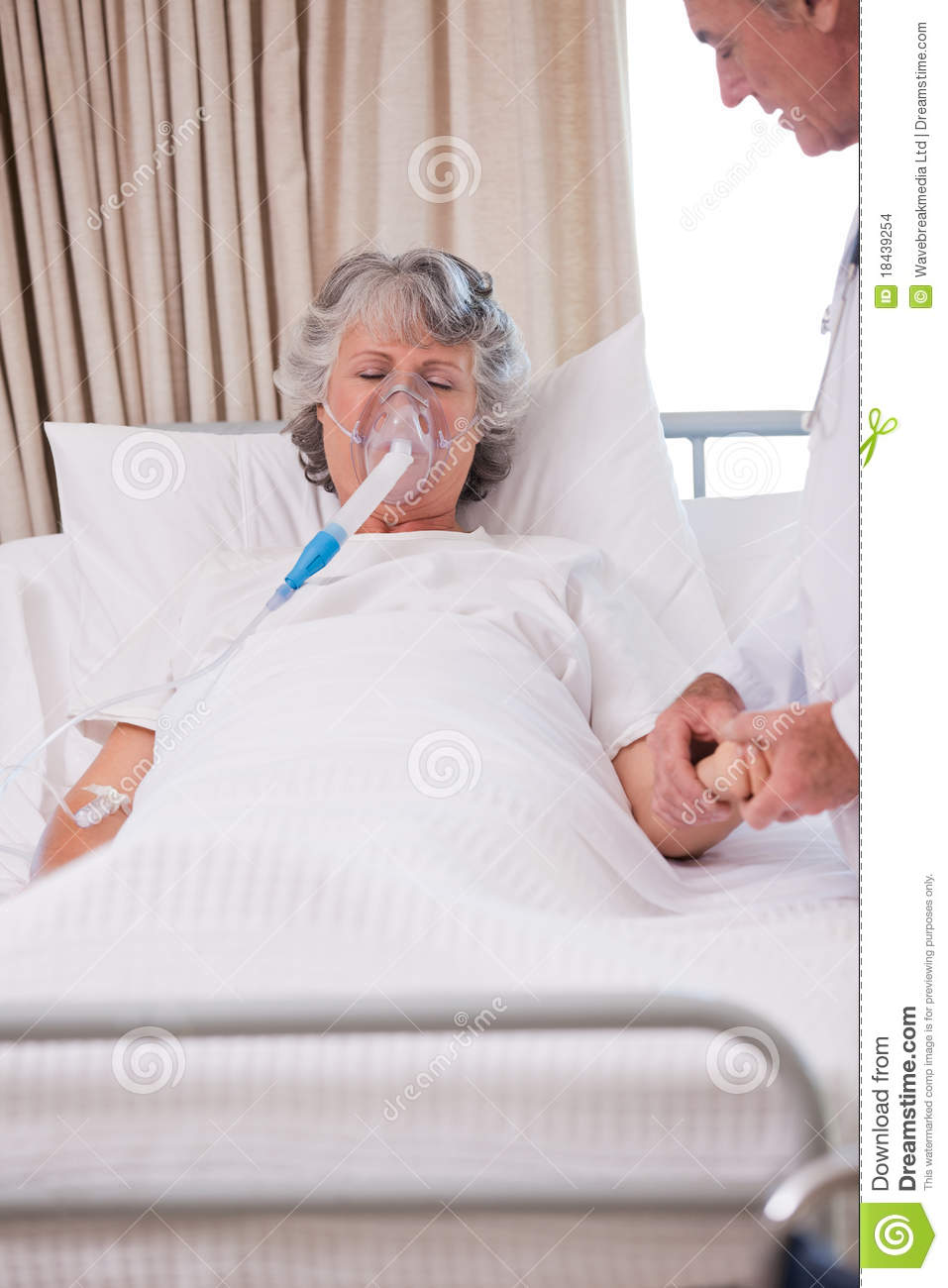 Senior doctor with his sick patient holding her hand.