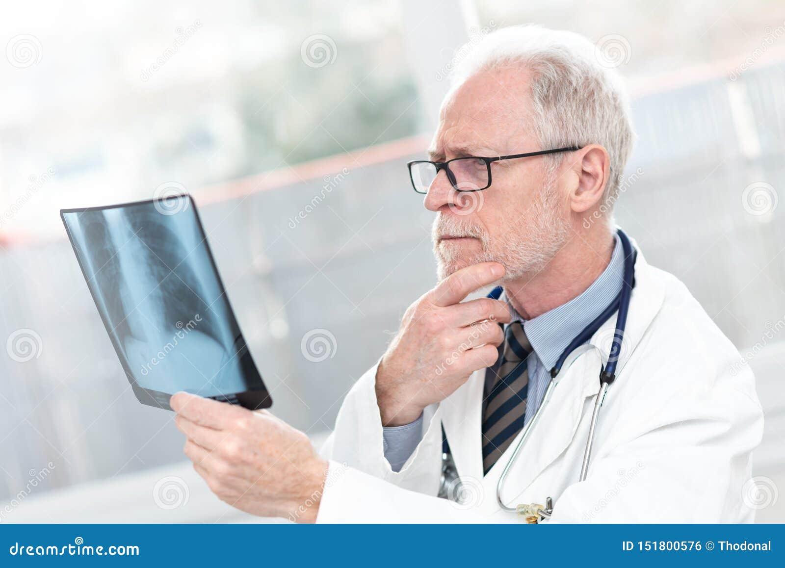 Senior doctor looking at x-ray