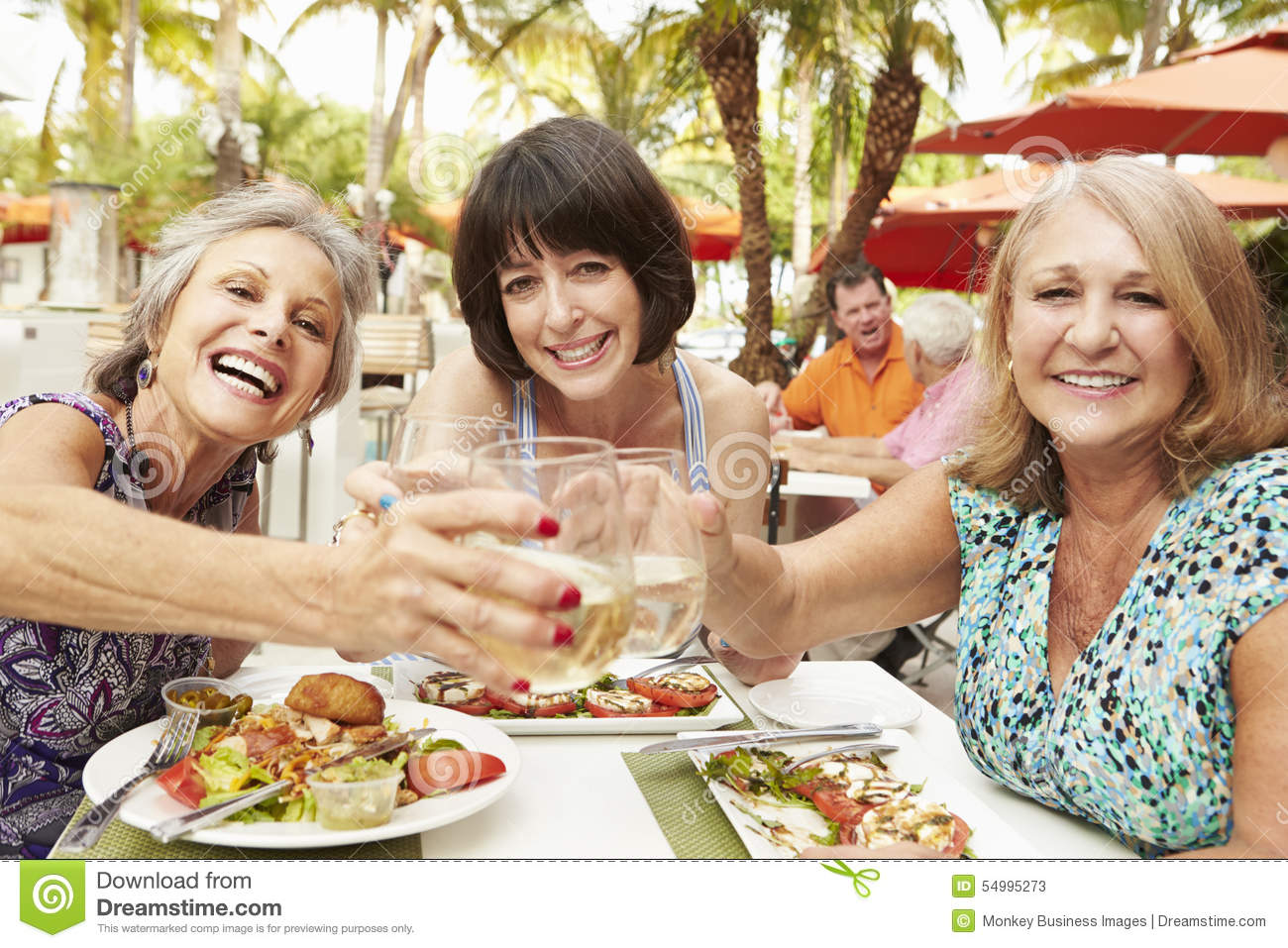Senior female friends eating meal in outdoor restaurant for Meal outdoors