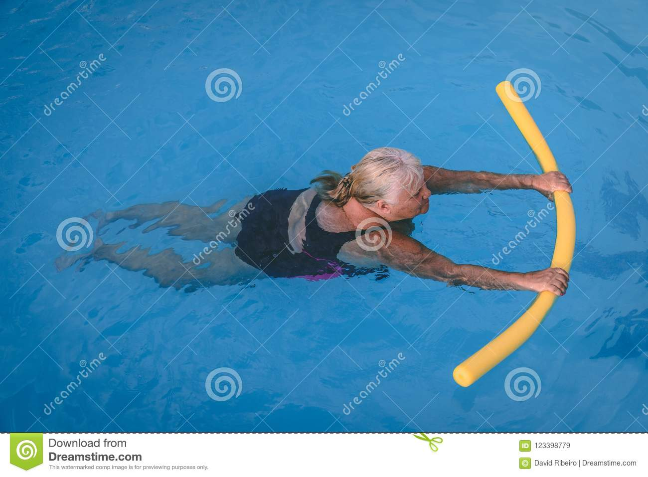 Senior female woman holds on to a flotation device on a swimming pool to learn how to swim