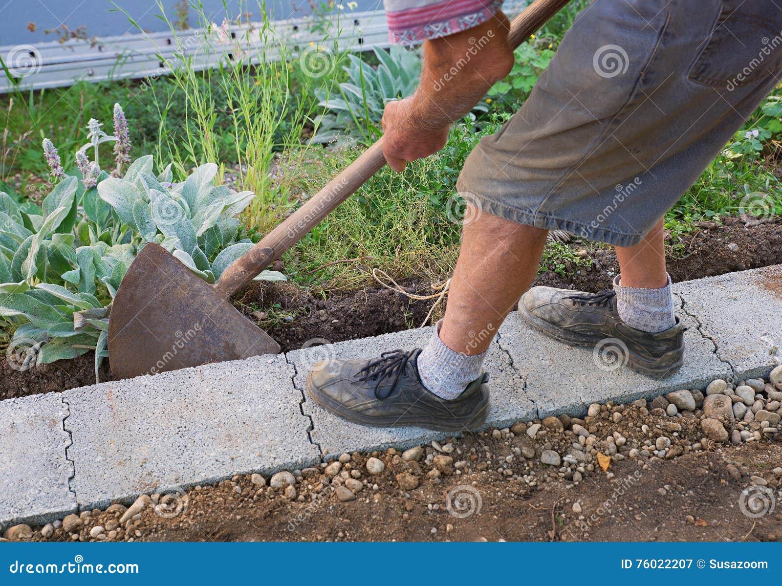 Senior gardener build a wall fundament