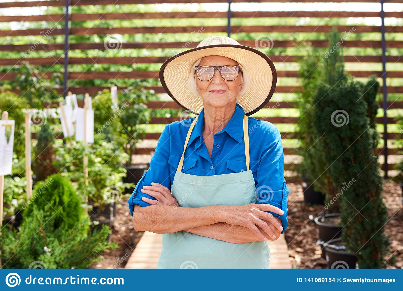 394835557e57b Waist up portrait of happy senior woman posing in garden standing with arms  crossed