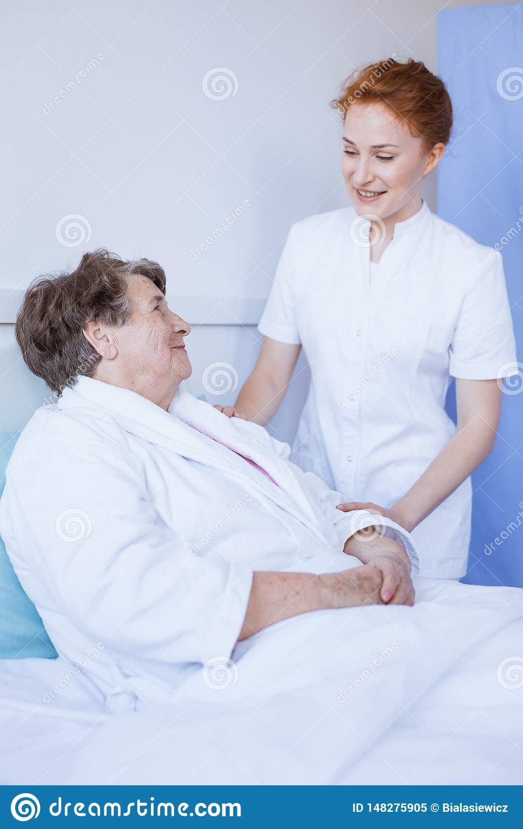 Senior woman lying in white hospital bed with young helpful nurse holding her hand