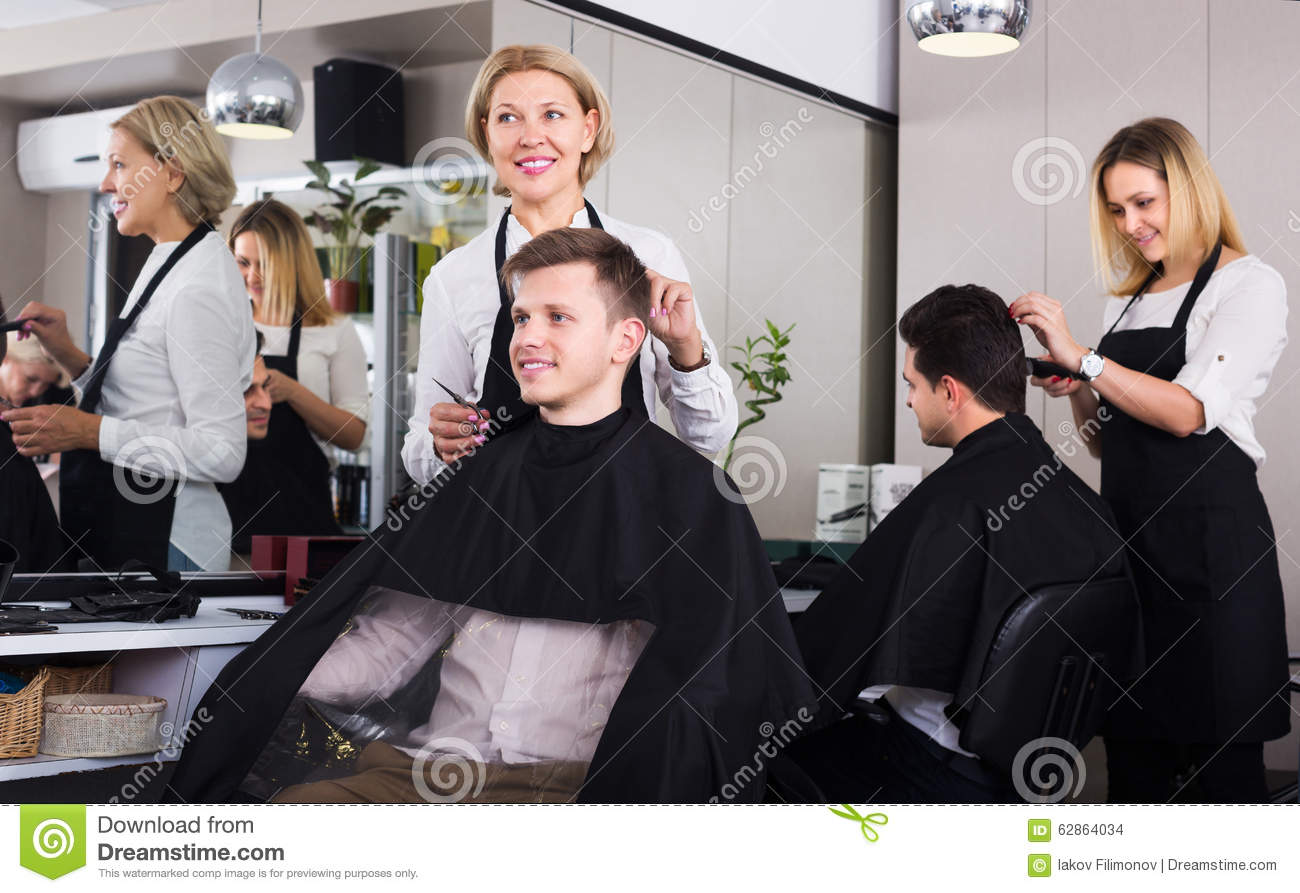 senior hairdresser serving teenager stock photo