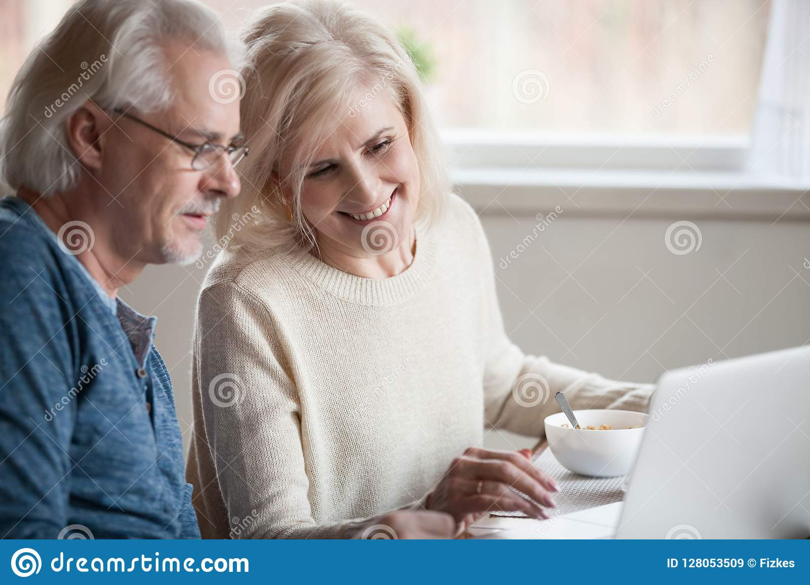 Senior happy couple enjoying using laptop eating breakfast toget