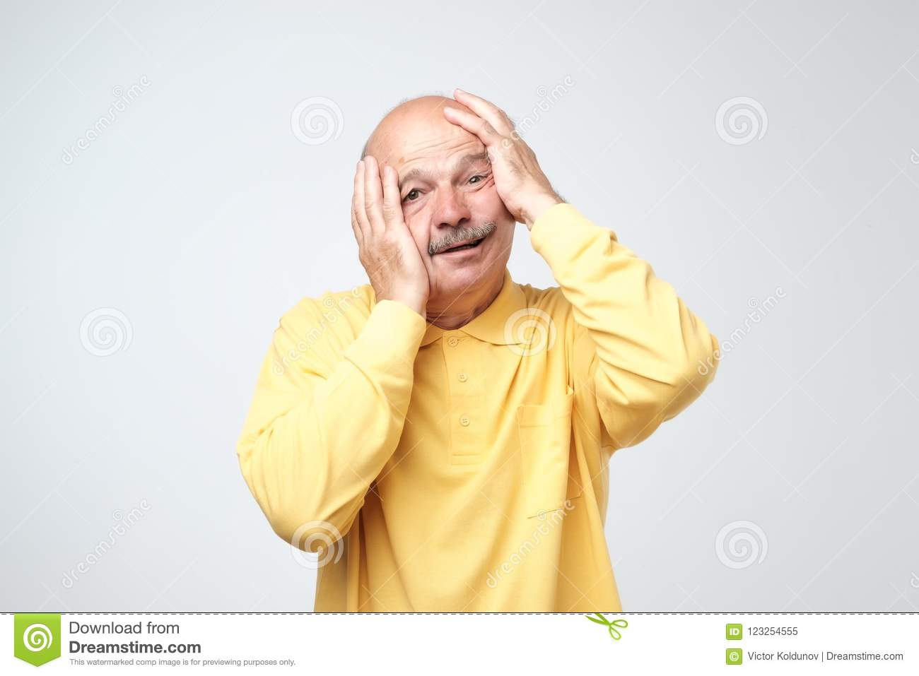 Senior Hispanic Man In Yellow Tshirt Pulling Skin On Face With Hands