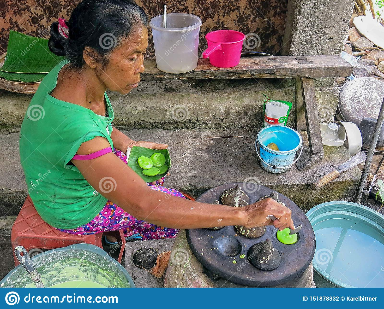 Senior Indonesian woman prepares traditional sweet dish. A very tasty dessert made from dough that is baked in stone form. Primiti