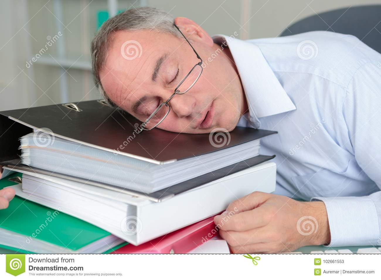 Senior male accountant sleeping on table