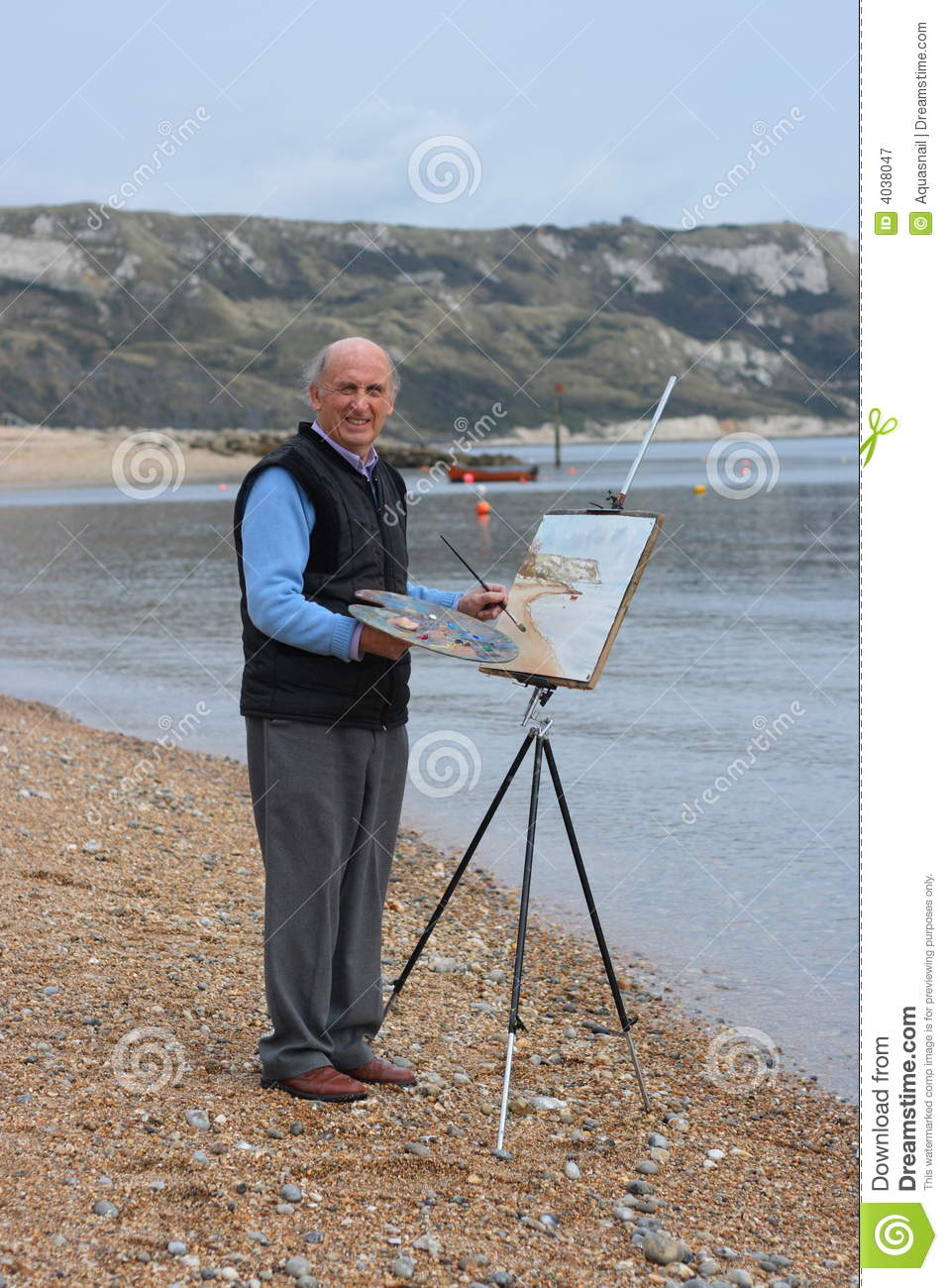 Senior male artist painting by the sea.