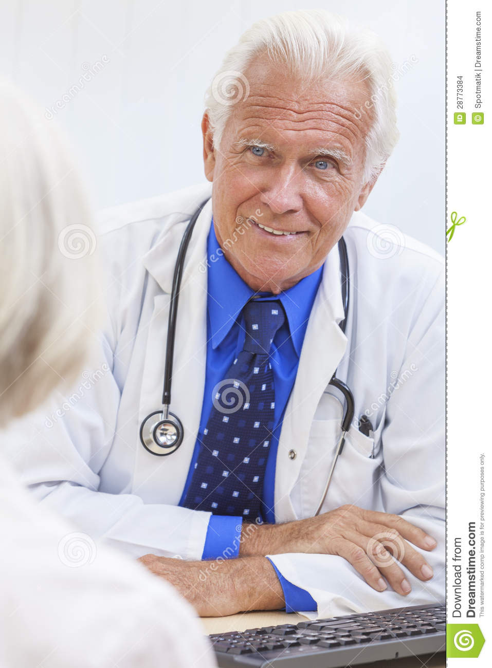 senior male doctor sitting at a desk in an office with a computer ...