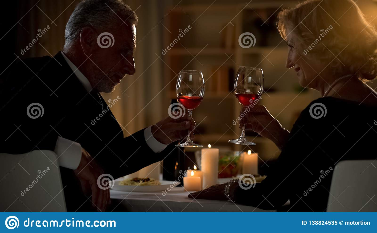 Senior male and female toasting with wine glasses, aged couple flirting on date
