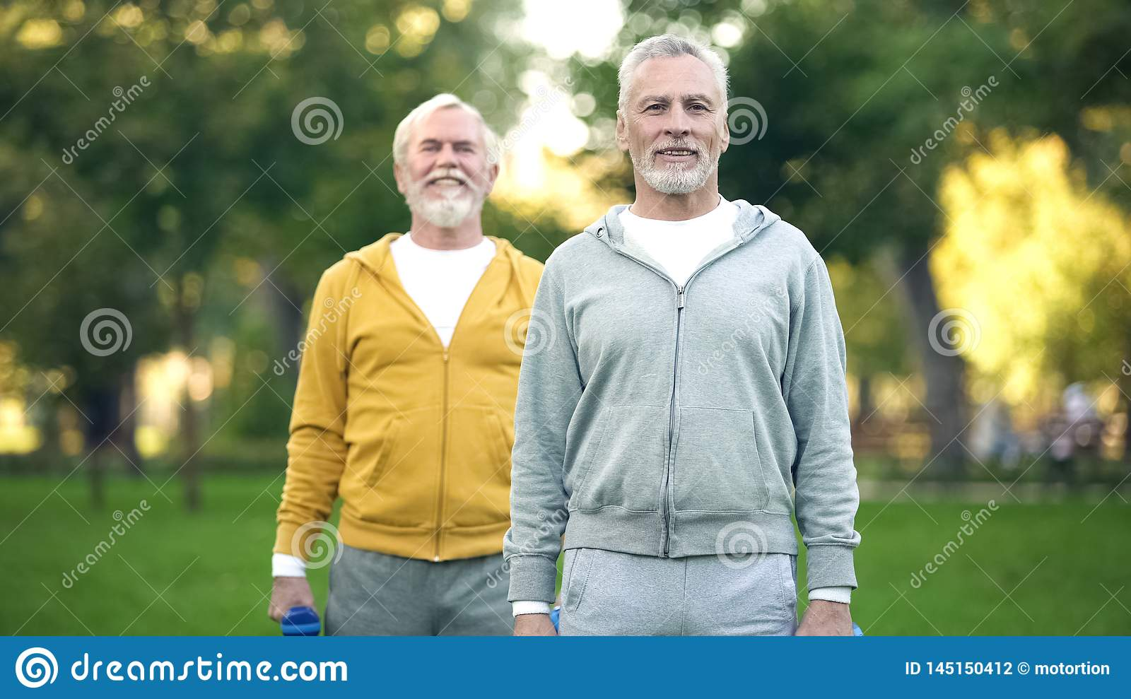 Senior male friends training in park, pumping muscles lifting dumbbells, health