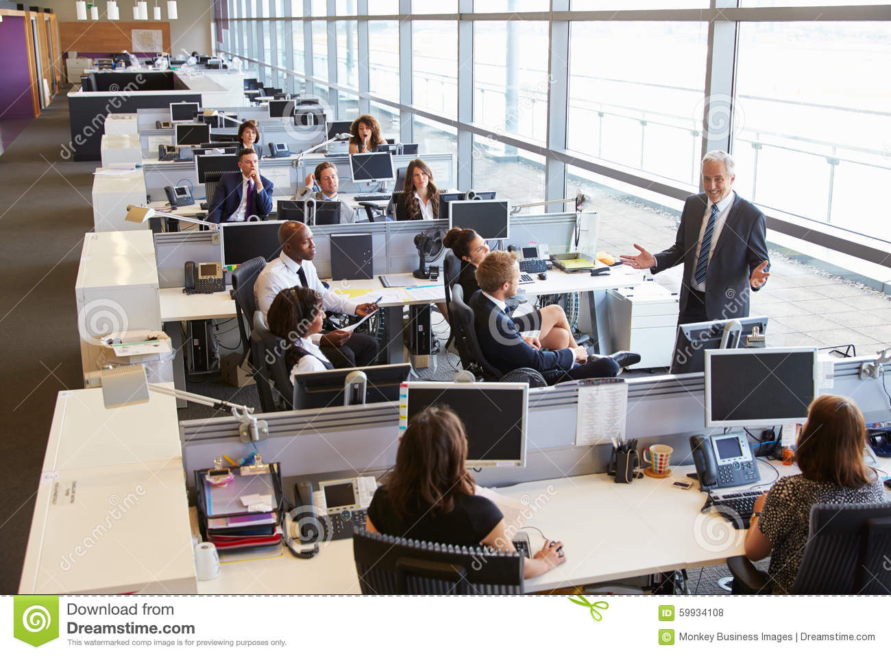 Senior male manager addressing workers in open plan office