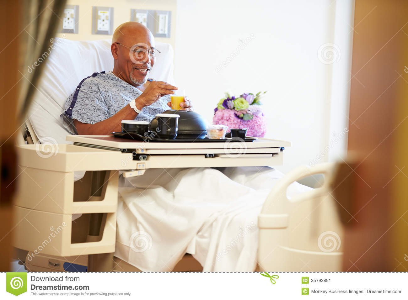 senior male patient enjoying meal in hospital bed stock