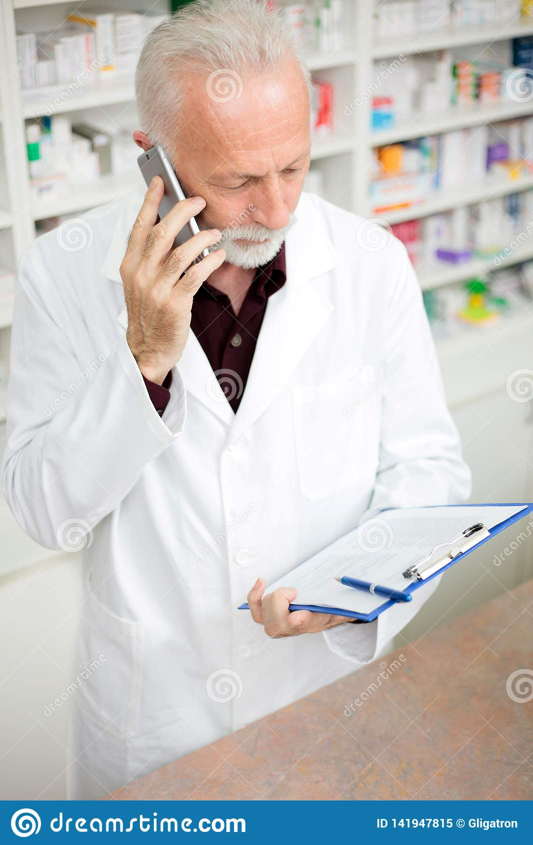 Senior male pharmacist talking on the phone and holding a clipboard