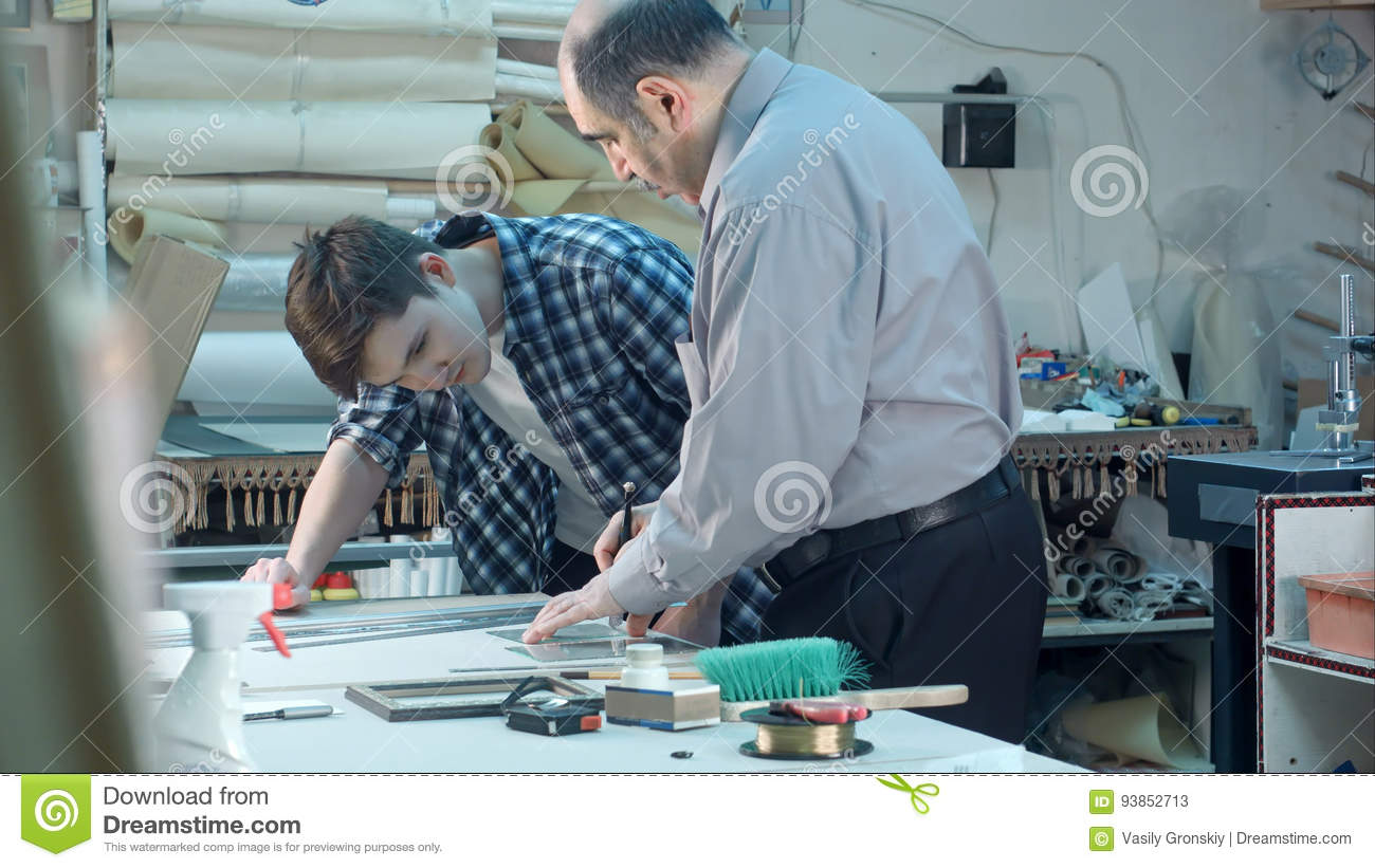 Senior Male Worker Instructing Young Trainee How To Cut A Glass For